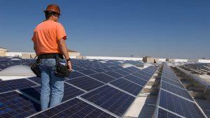 homem andando ao lado de placas fotovoltaicas no telhado